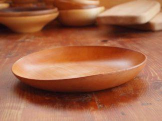 Grande assiette en bois de poirier, les bords sont irréguliers